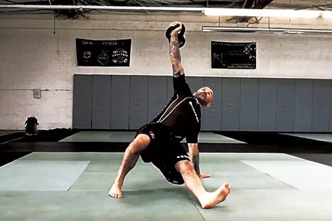 Joey Alvarado effectuant l'exercice Kettlebell Turkish Get Up.